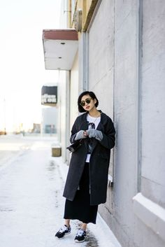 Alyssa Lau from the Ordinary People Blog wearing a long grey maxi coat, maxi skirt, t-shirt and Reebok runners
