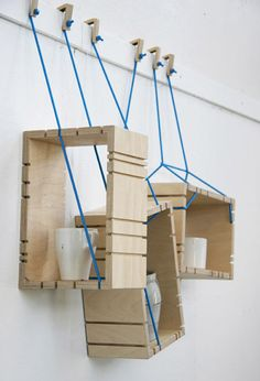 Parasite shelf by Johanna Landin - The system consists of plywood boxes suspended from wooden hooks on blue ropes, which pass through grooves in the outside of each box.