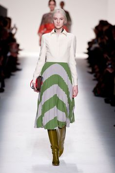 Valentino. 2014. 70s inspired outfit. Calf length striped skirt with high-gloss knee length boots, white shirt.
