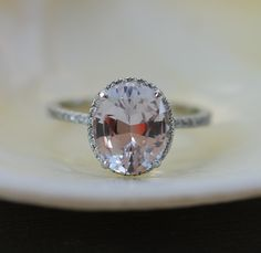 Smokey peach sapphire engagement ring. Engagement ring by Eidelprecious. This ring features a 3.83ct oval sapphire. The stone is natural non-treated sapphire, very rare. The color is gorgeous -smokey peach - very pretty, tones of sparkle! One of a kind. This beauty is set in my upgraded 14k white gold diamond setting with VS/F diamonds.  This ring is ready to ship. USPS priority to the US takes 2-3 business days. DHL to Europe takes 3-5 business days. Shipping within Canada takes 1-3…
