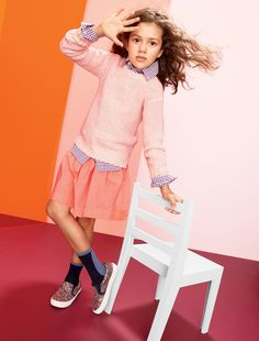 J.Crew girls' chunky neon sweater, pleated cotton skirt, and boys' washed in blue Tattersall shirt.