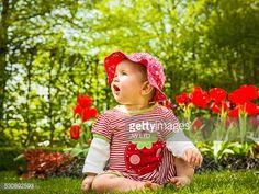 Stock Photo : 6-11 months, baby girl sitting in flower garden
