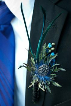 Boutonniere with thistle, blue wax flower, feathers