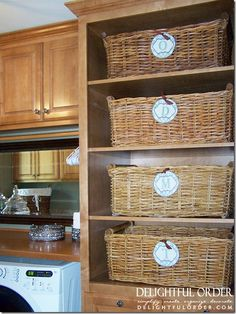 Large baskets in laundry room for clean and folded clothes, labeled with each family member's monogram. Great for large families!
