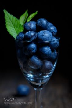 Blueberries with leaves in small glassBlueberries in small glass by jordachelr