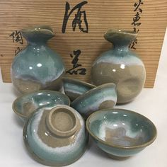 DESCRIPTION Gorgeous vintage Sake set consisting of a 2 Tokkuri (Sake Bottle), and five cups. Comes with the original wooden box. Beautiful and unique truly an excellent choice for the ones who love sake and traditional Japanese ceramics.  Artist`s signature is stamped on all cups and tokkuri  Sure to be a home decor conversation piece, as it shows the beauty and quality of Japan`s ceramic industry, which is world renown for its craftsmanship!  Size: Sake bottle 10cm  Cup height 3cm...