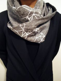 Looped scarf with geometric print on light grey linen. The never ending scarf with endless ways to style it. Can be worn through every season being