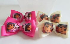 Kit com 4 laços (2 pares) de fita de gorgurão com fita estampada com a personagem Dora.