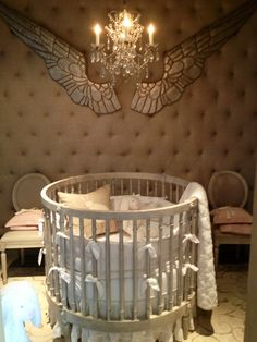 Minimalist White Wooden Round Baby Crib With Soft Bedding Accessories Decorating Also Awesome Beige Pillow And Luxury Chandelier Lighting On It