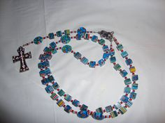 Rosary: Hail Mary: cube flower beads separated with 3 seed beads - silver, red, light blue. Our Father: oval flower beads separated with 6 seed beads same pattern