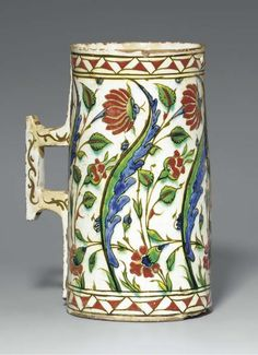 A LARGE IZNIK POTTERY TANKARD OTTOMAN TURKEY, CIRCA 1640 Of tapering cylindrical form with angular handle, the white body decorated with alternating large green and blue saz leaves and large red flowers curving to the left, with smaller red flowers in the interstices and a register of red flowers leaning to the right near the base, a band of interlocking red and white triangles at base and mouth, 9 7/8in. (25cm.) high Ceramic Mugs, Ceramic Pottery, Pottery Art, Ceramic Art, Stoneware, Turkish Art, Turkish Tiles, Glazes For Pottery, Pottery Bowls