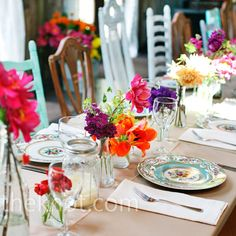 Tablescape: Long, rectangular table, white  cloth, brown paper runner, a line of mismatched jars and candles own the middle