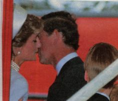 Prince Charles gives Princess Diana a kiss.