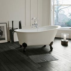 What a beautiful roll top bath! Love the contrast of clean white, black vintage feet and dark wooden flooring. So inviting!