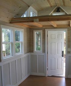 Knotty pine ceilings, wainscoting, and cork flooring give this tiny house interior a unique look.