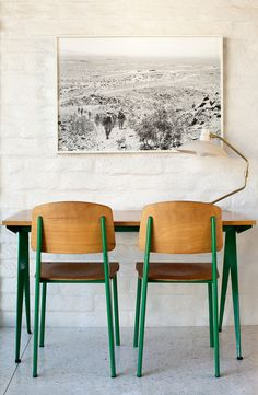 love the green on the chairs and table. the large scale photograph blends seamlessly into the wall.