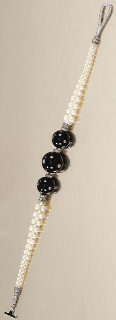 AN EARLY ART DECO SEED PEARL, ONYX AND DIAMOND BRACELET, CARTIER, CIRCA 1915. Designed as three graduated onyx spheres embellished with circular-cut diamonds, interspersed with diamond rondelles to a tapered woven seed pearl bracelet, terminating in a diamond and onyx loop and bar clasp, signed Cartier and numbered. #Cartier #ArtDeco #bracelet