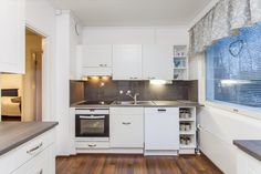 Kitchen. White cabinets, white household appliances, light grey countertops and large, grey tiles. ~ from Etuovi.com