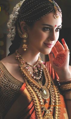 Indian multi-strand tikka bridal jewelry with layered gold necklaces - Minmit.com - More here - www.indianweddingsite.com/10-maang-tikka-jhoomar-looks/
