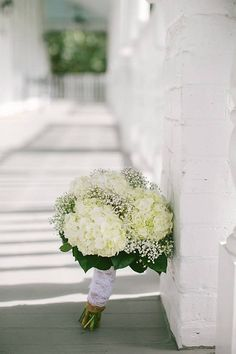 Bride's bouquet - White hydrangeas, babies breath and greenery. Stems wrapped with burlap and lace.