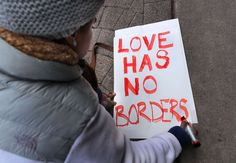 """Protests against Trump's immigration ban: Tori Furtado, from Boston, kneels down to write a sign that reads, """"Love has no borders,"""" in front of the Chinatown Gate in Boston, on Jan. 28."""