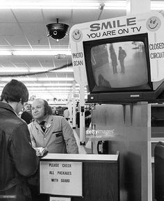 NOV 27 1972; In - store Television System Keeps Constant Vigil - Security guard Tony Diamond is aided in watch for shoplifters at target Store by five - lens camera on ceiling. TV at entrance warns all cameras are watching.;