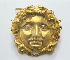 Medusa brooch, from the tomb of Philip II (c.336BCE) is a gold brooch depicting Medusa with four snakes to avert evil, used to pin on to linen armour. Museum of the Royal Tombs, Aegae. Macedon.