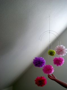 6 poms gently float and spin on this silver wire framed mobile #pompom #mobile #colorfull