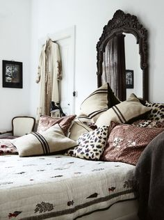 An old Indian mirror over a bed covered with a pile of pillows