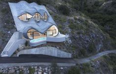 CASA DEL ACANTILADO, SALOBRENA, SPAIN Here's a house that will never go unnoticed. Embedded into the face of a cliff, the Casa Acantilado (House on a Cliff) takes on the form of a scaly three-eyed monster. The property's main feature would have to be its roof, which takes up the entirety of its exterior facade, reminding us of the fantastical architectural creations of Spain's most renowned architect, Antoni Gaudi.