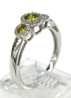Ladies 14kt white gold diamond ring. Ring is set with 3 brilliant round cut color treated yellow diamonds weighing .25ct and 37 brilliant round cut white diamonds weighing .40ct. A total of approximately .65ct.