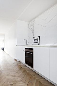 A beautiful herringbone wood floor warms up white and marble in a kitchen from Frederic Berthier | A Gallery of Minimalist Kitchens