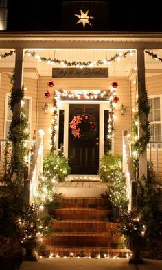 Lighted christmas decorated porch with greenery. Like the hanging joy to the world sign as well