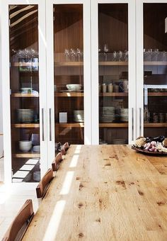 rustic modern kitchen; natural wood interior shown through painted glass floor to ceiling cabinetry