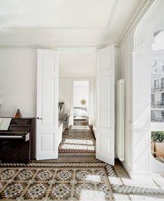 Double doors, geometric design carpets, piano