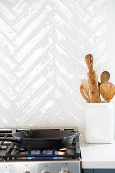 White herringbone backsplash tiles are mounted to a cooktop over a stainless steel oven range placed beside blue cabinets topped with a white countertop. Chevron Kitchen, Blue Kitchen Tiles, Wood Tile Kitchen, Kitchen Design, Kitchen Backsplash, Kitchen Ideas, Backsplash For White Cabinets, White Countertops, Blue Cabinets
