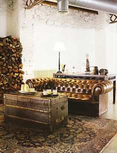 Chesterfield sofa, Louis Vuitton vintage trunk as low table on a Persian carpet.