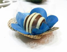 Forminha F1T1C Azul turquesa e dourada  Forminhas em tecido para doces finos.  Camélia 5 pétalas.    Dimensão do produto: 8 cm  Fundo 3 cm    Duas camadas.    COR:  Tela: Dourada  Cetim: Azul turquesa    Doce não incluso.