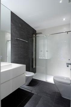 Piso negro, lavabo blanco, muebles blancos, cancel de regadera templado, regadera alargada de aluminio.