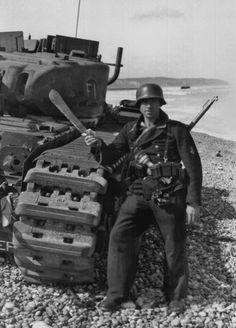 Kriegsmarine Bootsmann wielding a bolo knife next to a KO'd Churchill tank. Taken shortly after the failed Dieppe Raid - 1942