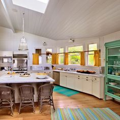 the shape of this kitchen along with the wood and softly bright colors makes me speechless.