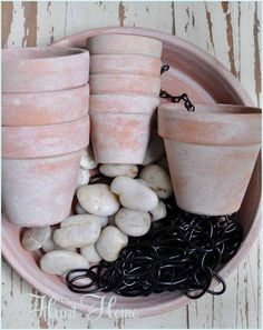 Rain Chain ~ DIY Rain Chains guide rain water down chain links making beautiful water displays.Make this one using chain, terra cotta pots and a saucer filled with pebbles.