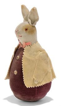 AN EARLY ROLY-POLY RABBIT, white velvet head with brown patches, orange and black glass eyes, red stitching, purple velvet weighted body, pinked yellow velvet jacket and pink ribbon --5½in. (14cm.) high (slight fading)