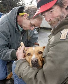 Vets help homeless care for pets: Ken Isgrigg (right), who is homeless, holds JoJo as a vet tech gives the dog shots