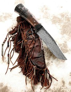 Primitive Damascus Belt Knife with Quilled Wheel Sheath by Daniel Winkler.  Primitive damascus belt knife with a rawhide covered elk antler handle. The sheath is rawhide covered and heavily decorated featuring a quilled wheel.