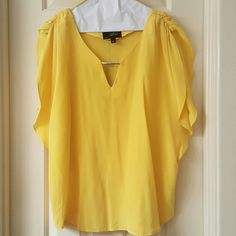 Akiko yellow blouse Akiko yellow blouse with gold metal detail in front. 100% silk brand new with tags akiko Tops Blouses