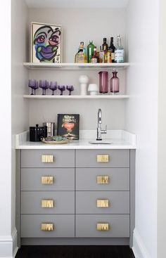 Wonderfully designed gray contemporary wet bar is fitted with gray flat front drawers accented with gold pulls and a white marble countertop finished with a small curved sink paired with a polished nickel faucet mounted under stacked white shelves.