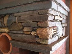This is a chimney that has been built for a wood stove hook up in the basement and the first floor, which is pictured here.  There is a tall narrow built in wood box and a stone ordained mantle.  I used stone and beach glass in this piece that was gathered by the home owner from all over the world.  I loved working with all the different pieces of stone that he had collected over the years.