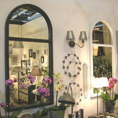 Superbe miroir en forme d'arcade en manguier peint, ton gris très actuel ou blanc plus classique. Large miroir rectangulaire en bas, en demi cercle en haut, comme un fenêtre ouverte sur l'extérieur. A la fois classique et original, ce miroir apporte une impression d'espace et agrandira une pièce. Création Jardin d'Ulysse