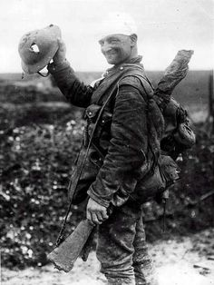 """1914-1918:  Hole in a helmet.  """"Saved by shrapnel helmet. This soldier, on the way to hospital after being bandaged at Field Dressing Station, shows the helmet which saved his life."""""""